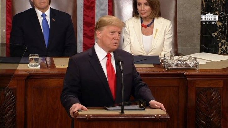 President Trump speaks from the lecturn on the floor of the U.S. House of Representatives. Behind him Speaker Nancy Pelosi, D-Calif., wears suffragist white.