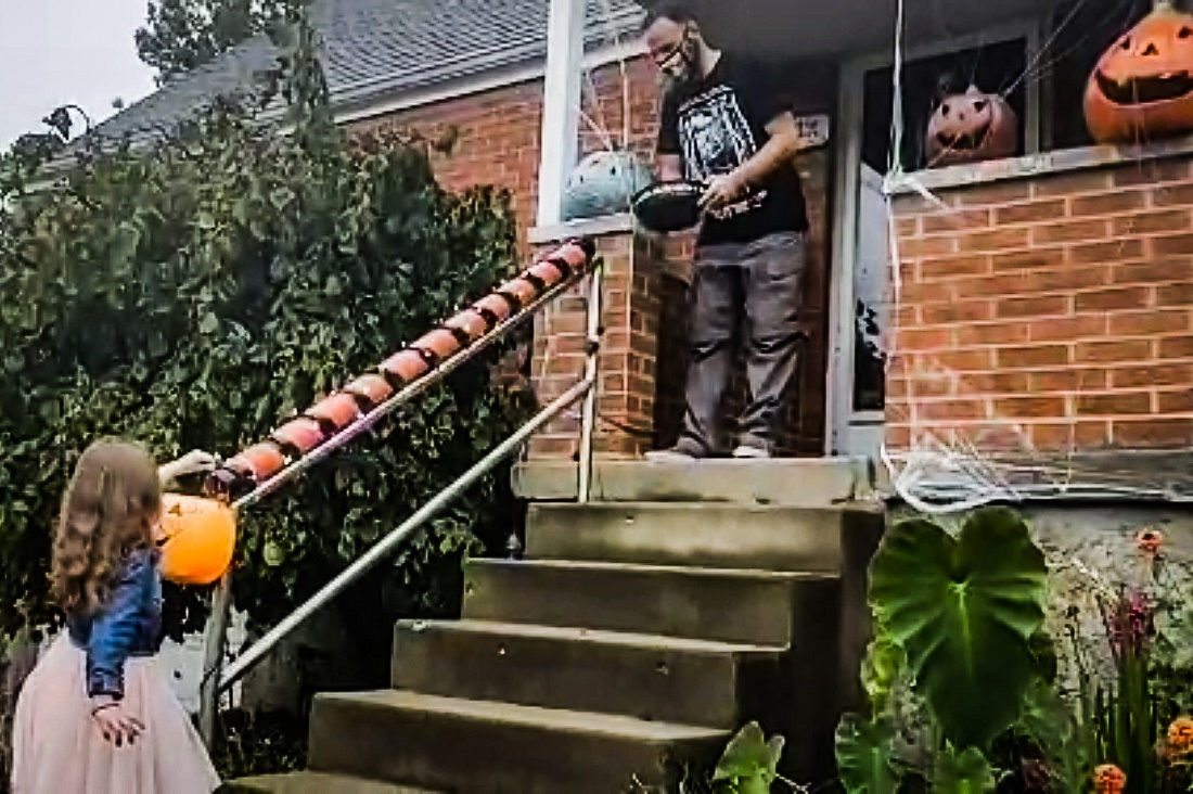 "A homeowner gives Halloween candy at a safe distance to a trick-or-treater using a homemade ""Halloween chute"" attached to a hand rail next to front steps at a house."