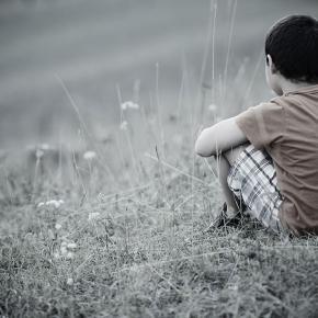 Boy sitting alone in grass