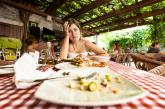 Girl sitting at table with empty plates of food