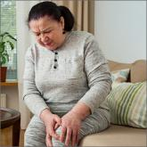Woman holding her knee in pain on a couch