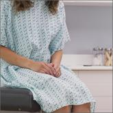 Woman sitting in medical gown on table in office
