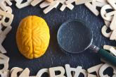 Brain next to magnifying glass with wooden letters surrounding