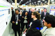 "Masih Shinwa, MD, explains his abstract, ""Please 'THINK' Before You Order: A Multidisciplinary Approach to Decreasing Overutilization of Daily Labs,"" to inquiring passersby during Tuesday evening's RIV poster session."