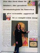 Dr. Leslie S. Baumann in her office, in front of a Camay soap ad from the 1920s.