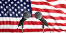 Two microphones against a backdrop of the American flag