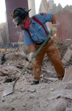 A New York firefighter digs through the rubble at Ground Zero while wearing a protective mask.