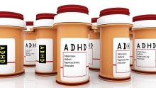 Opaque pill bottles with red lids and ADHD and attention deficit hyperactivity disorder written on them