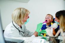 A doctor, wearing a mask, tends to a toddler whose mother is wearing a mask.