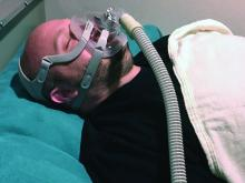 A man wears a CPAP device