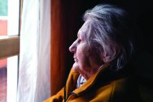 depression in the elderly: An elderly woman gazes out the window.