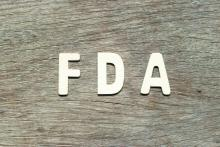 FDA written in white letters on a wood background.