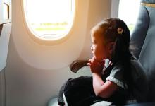A young girl looks out the window of an airplane