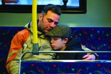 Foster care father and son embrace on bus