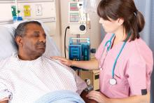 A health care provider tends to a patient in a hospital bed.