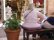 An obese woman sits on a bench