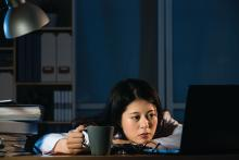A sleepy doctor holds a coffee mug while looking at her computer.