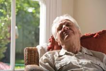An elderly man sleeping in a chair.