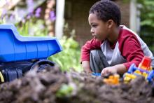 boy playing with toys in the yard and dirt