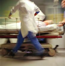 a scene from an emergency dept., with people rushing and a patient on a stretcher