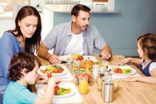 Family gathered around the table with autistic child