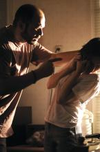 An incident of domestic viokence is shown, with a man threatening his partner.
