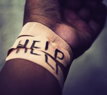"""A wrist is shown wrapped in adhesive bandages with the word """"HELP"""" spelled out across them."""