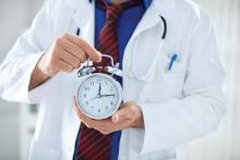 A doctor holds an alarm clock.