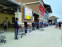 Shoppers wait in a long line outside a grocery store in Houston during the COVID-19 pandemic.
