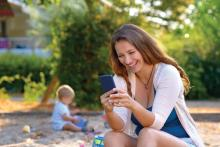 A young mother uses a smartphone while her baby son plays nearby with his toys