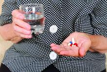 A woman prepares to take a handful of pills.