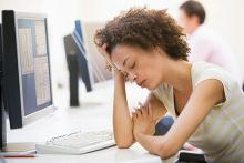 A young woman is shown sleeping in front of computer