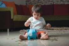 Young child sitting on the floor and putting a coin into a piggy bank.