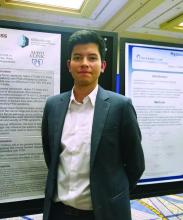 Freddy JK Toloza, MD, standing in front of his poster
