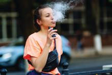 A young woman uses a vaping device