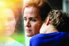 A worried woman holds a young boy while looking through a window