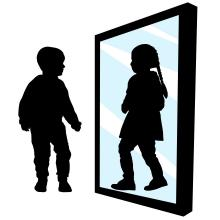 Boy sees a girl in the reflection of the mirror.