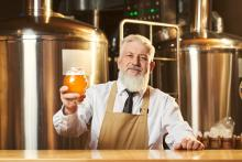 man in brewery holding a beer
