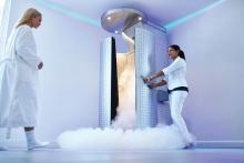 A woman approaches a cryotherapy chamber