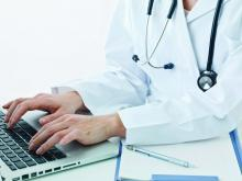A doctor enters information into an electronic health record.