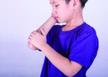 Young boy in pain holding his elbow