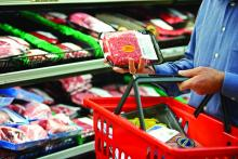 A shopper reads the label on a package of red meat.