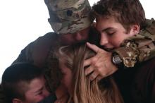 Lt. Col. Eric Westby hugs his children before deploying at Little Rock Air Force Base, Ark.