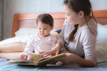 Mother reading a book to her child on the bed. Bedtime story. Learning how to read.
