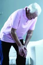 An older man bends over in pain with his hands on his left knee.
