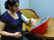 A pregnant woman uses a blood pressure monitor.