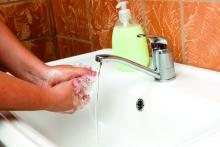 A woman is shown at a sink washing her hands.