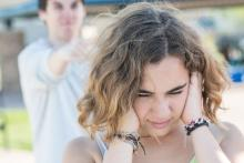 Teenage girl with her hands covering her ears while her boyfriend is yelling at her