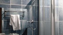 Reflection of towel rack is seen in a bathroom mirror
