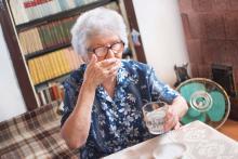 An elderly woman takes pills